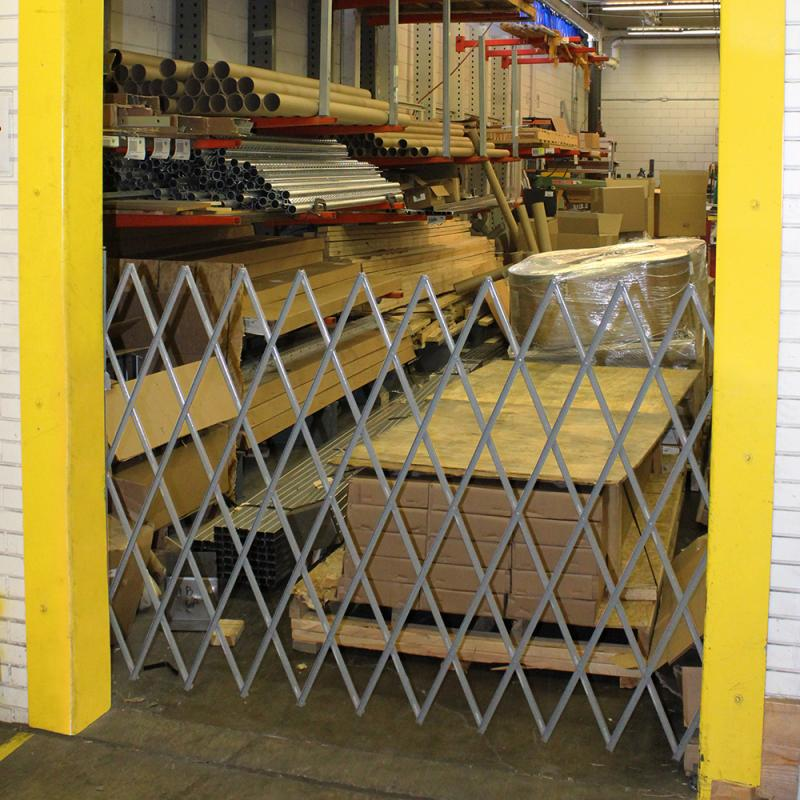 Expandable, folding security gate across door opening