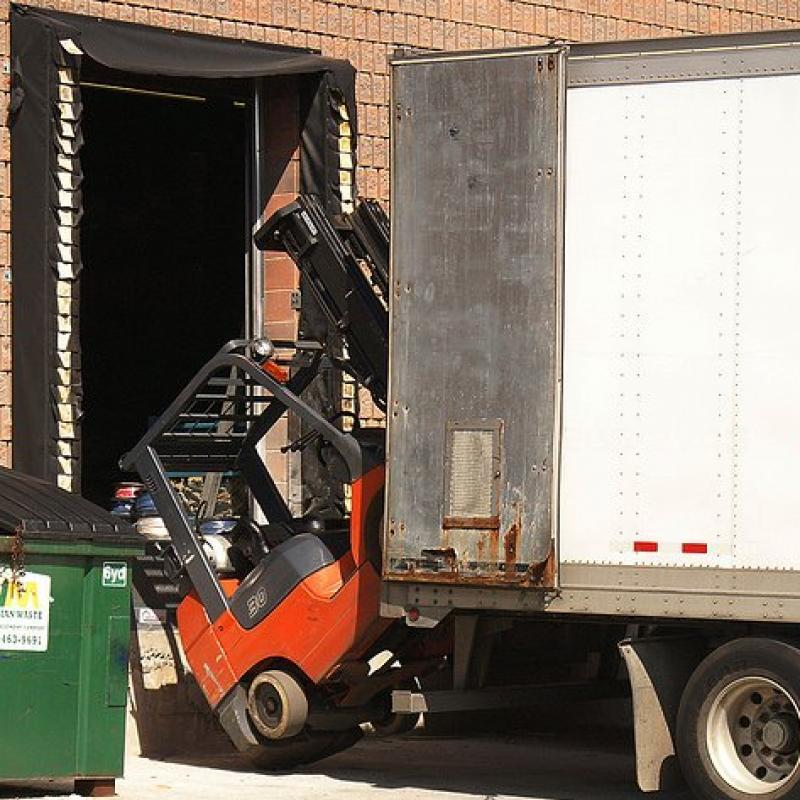 Forklift falling off an open dock, due to early departure of unsecured trailer bed