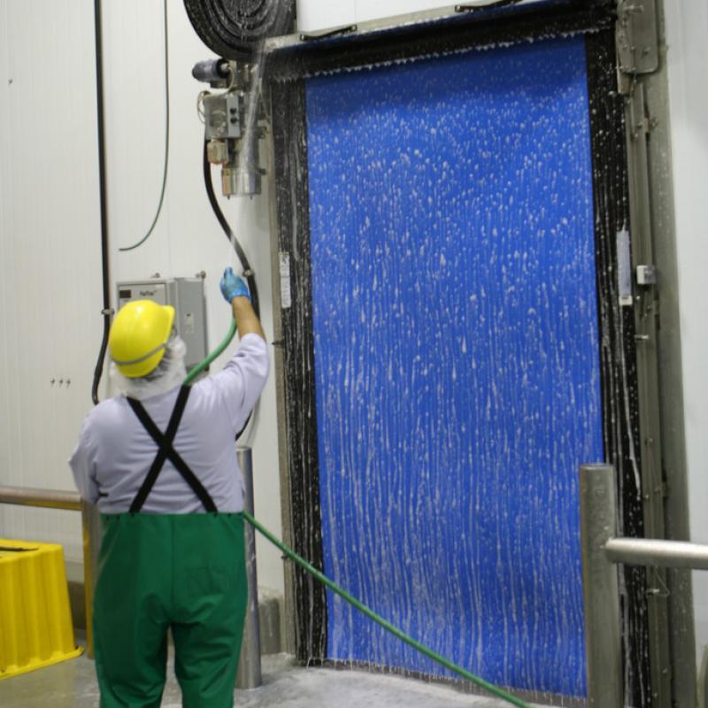 Employee spraying down FasTrax Clean door
