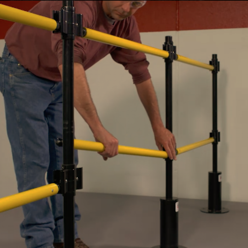 Dock worker adjusts the removable GuardRite Retractable Barrier