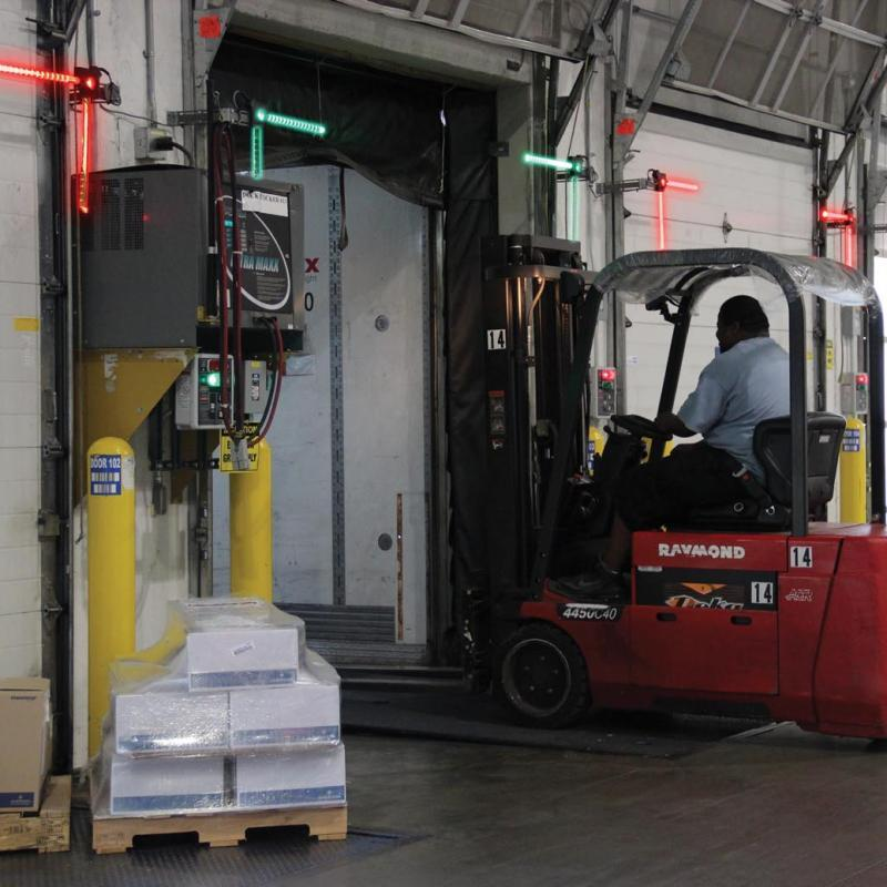 Forklift traveling through green-lit Loading Dock opening